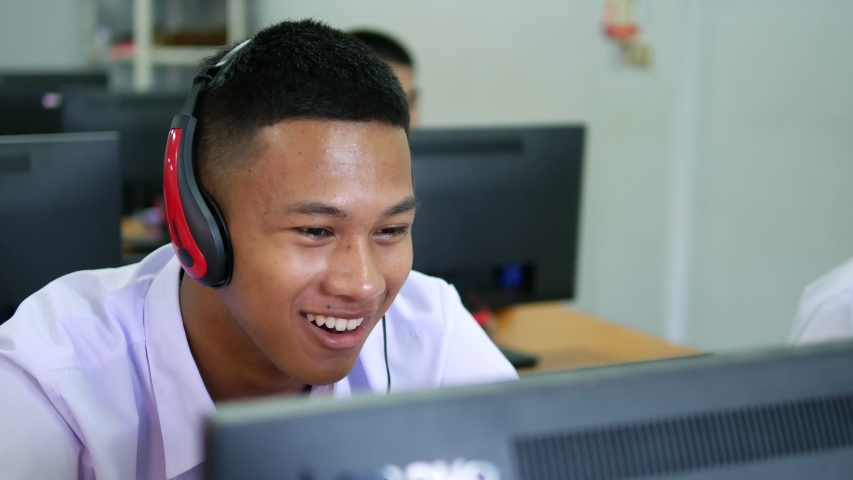 Asian high school male students wearing headphones are laughing and enjoying social media in computer class.   Shutterstock HD Video #1029995420
