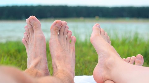 Close up of young couple feet relaxing on beach. Woman. Man. Lake. Landscape. Legs. Blur Background