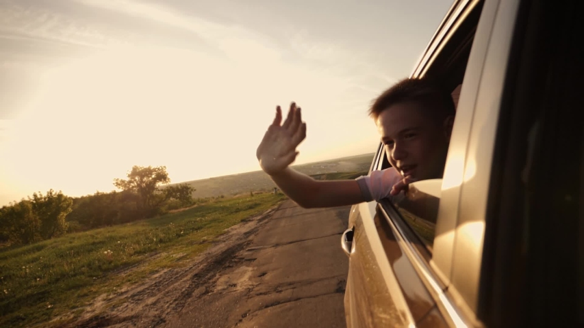 The boy looks out of the car window traveling the world. The boy's face in the sun with an arm stretched out of the car window. The concept of a happy family. Pursuit of travel and entertainment | Shutterstock HD Video #1030057760