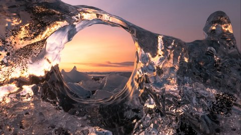 Timelapse of Ice sea waves sunrise on ocean - creative frame idea, view from crystal clear iceberg to ocean waves and people moving. Adventure atmosphere of travel to winter Iceland destination