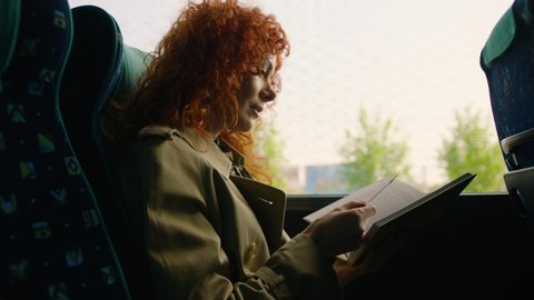 Woman travelling by bus and reading book. Woman is traveling in the bus in front of the window. Shot on Arri Alexa Mini Cinema Camera.