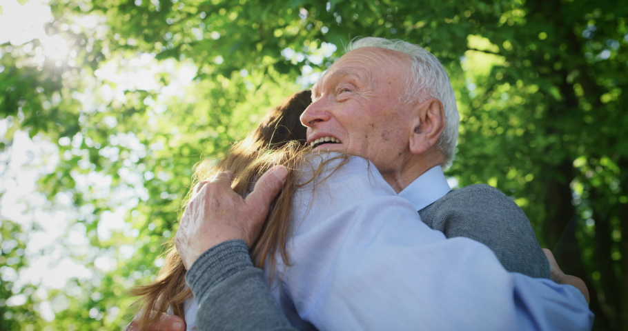 Slow motion of happy granddaughter is giving an effective hug to her grandfather as a sign of love and respect in a green park on a sunny day. | Shutterstock HD Video #1030112870