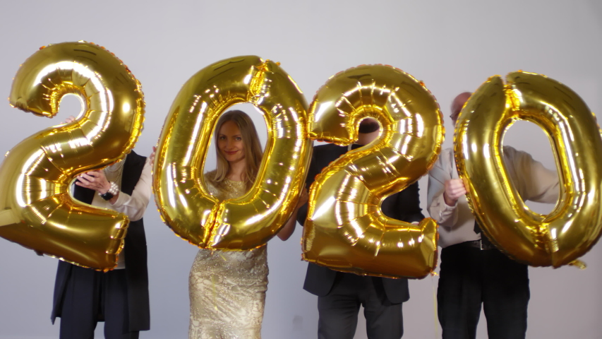 Medium shot of happy people standing against grey background and dancing while holding number 2020 golden balloons   Shutterstock HD Video #1030114310