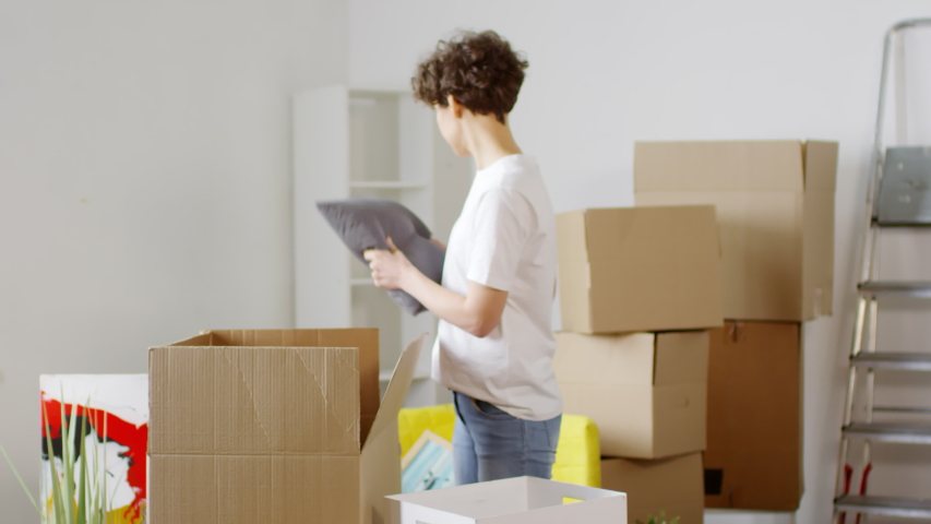 Panning medium shot of 30-something Caucasian man bringing in cardboard box and helping his girlfriend who is unpacking their stuff in their new dream home after moving in together   Shutterstock HD Video #1030123940