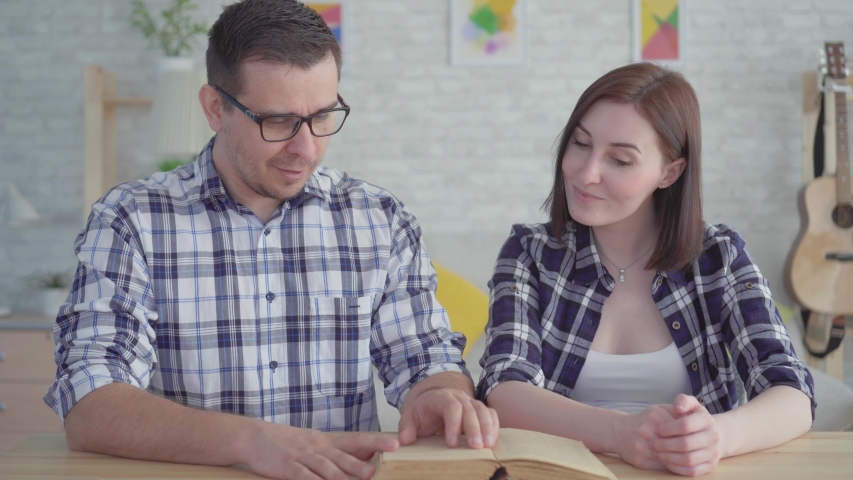 Close up young couple reading and studying a book in a modern apartment | Shutterstock HD Video #1030195760