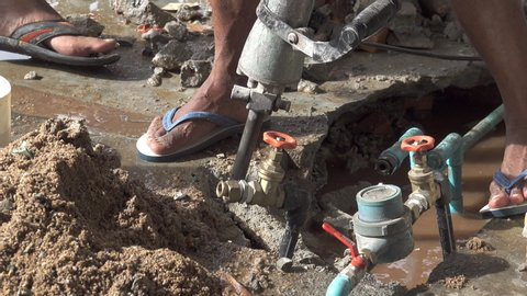 Worker drilling concrete floor  with jackhammer repairing leakage of underground  water pipeline.    Closeup of plumber fixing service,4K video zoom in.