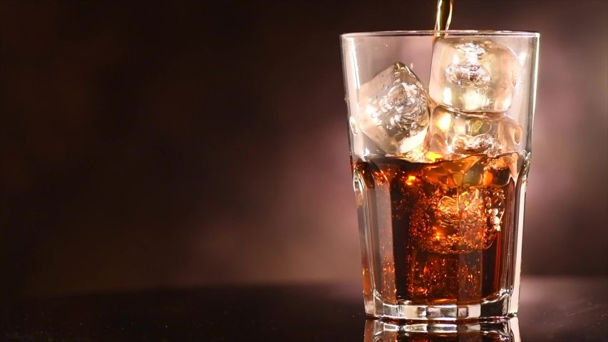 Pouring Cola with ice cubes close-up. Cola with Ice and bubbles in glass. Coke Soda closeup. Food background. Rotate glass of Cola fizzy drink over brown background. Slow motion 4K UHD video footage