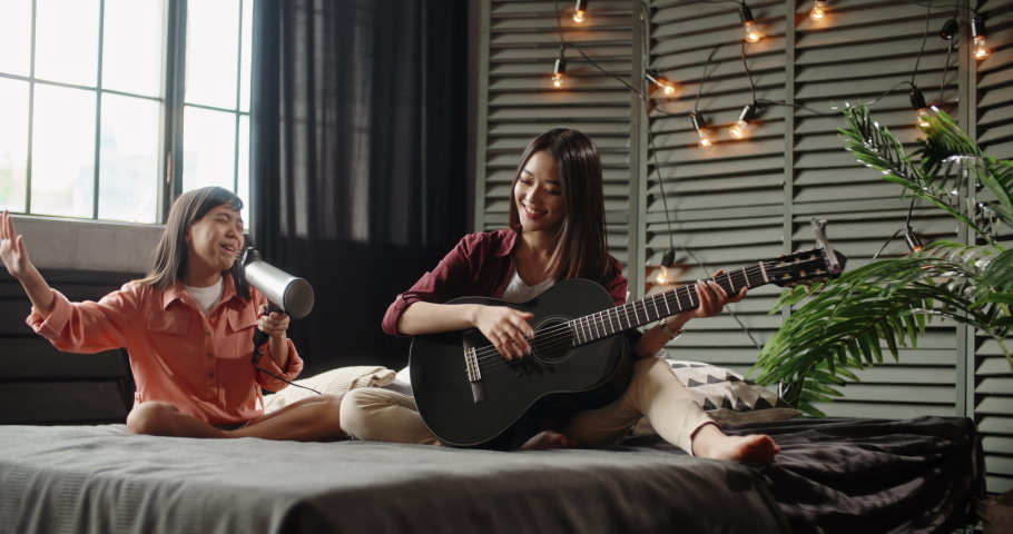 Two asian sisters sitting on bed, elder playing guitar while little kid is singing into hairdryer. Friends having fun spending time together at home - recreational pursuit, family time 4k   Shutterstock HD Video #1030221530