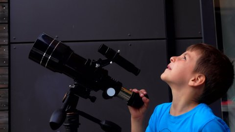 Little boy examines the sky through a telescope on a sunny summer day.