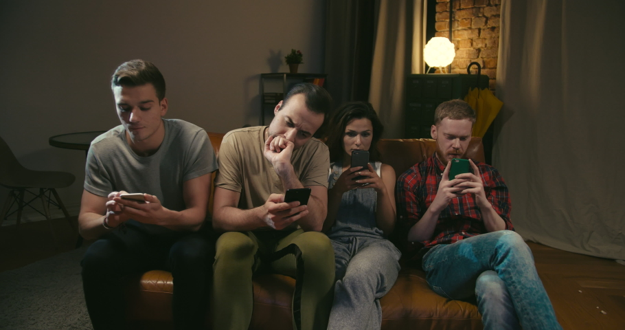 One female and three male caucasian friends are bored, scroll and text with their smartphones during commercial on TV at night in dark room. Terrible party | Shutterstock HD Video #1030305800
