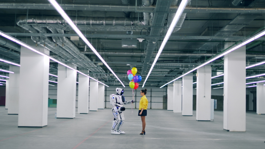 Young woman gives colorful balloons to a white robot.  | Shutterstock HD Video #1030374440