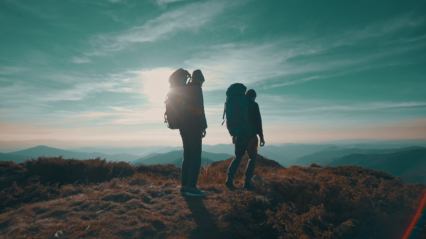 The hikers walking to the mountain on the sunset background. slow motion   Shutterstock HD Video #1030416170