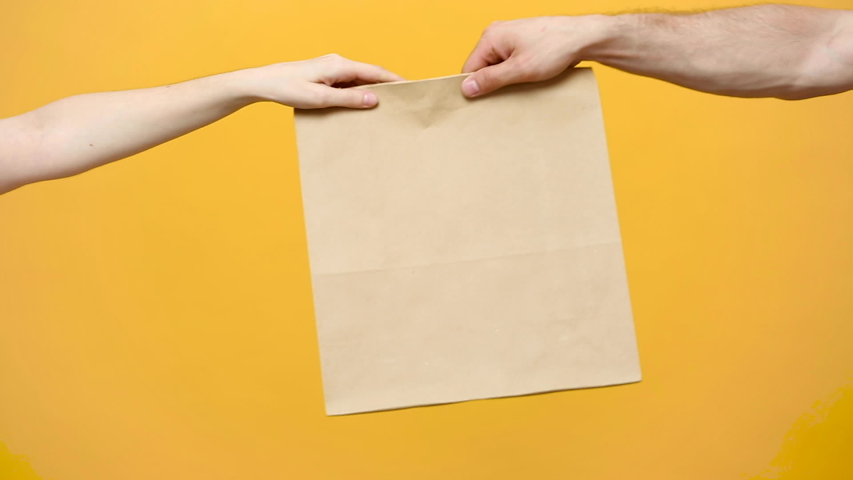 Close up female hold in hand brown clear empty blank craft paper bag for give takeaway isolated on yellow background. Packaging template mock up. Delivery service concept. Copy space. Advertising area | Shutterstock HD Video #1030487360