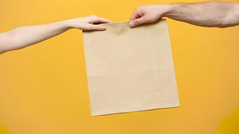 Close up female hold in hand brown clear empty blank craft paper bag for give takeaway isolated on yellow background. Packaging template mock up. Delivery service concept. Copy space. Advertising area
