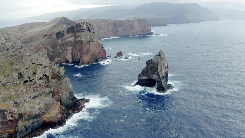 Descending aerial view above the coastline Of Madeira With High Cliffs Along The Atlantic Ocean waves breaking against the rocky terrain.