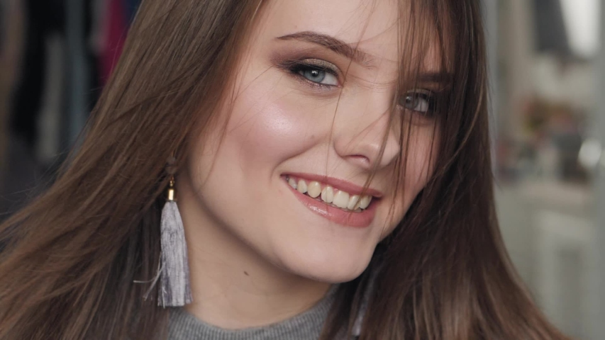 Closeup slow motion portrait of young beautiful brown haired woman with blue eyes adorable smile with natural makeup having fun in her room indoors looking at camera hair fluttering in the wind #1030541120