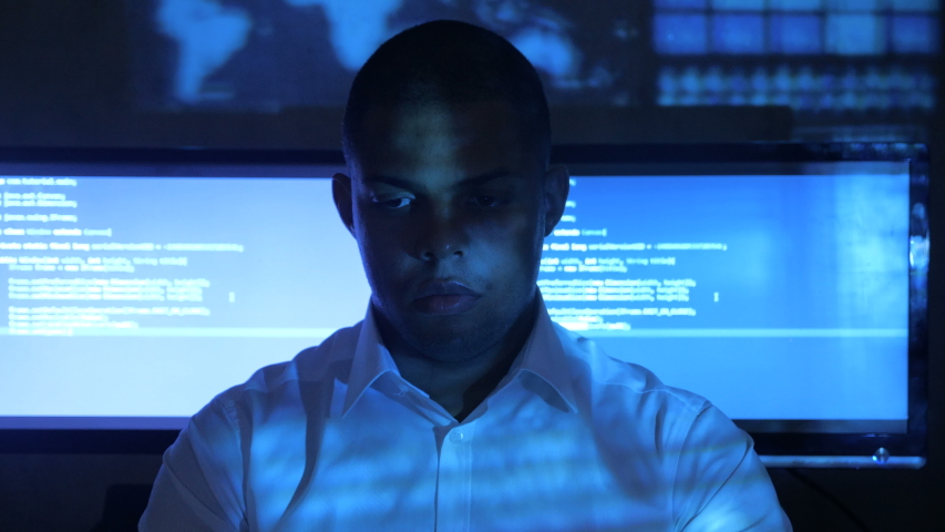 Portrait of African American man programmer in white shirt working on computer in security data center. Holographic code on his face | Shutterstock HD Video #1030563170