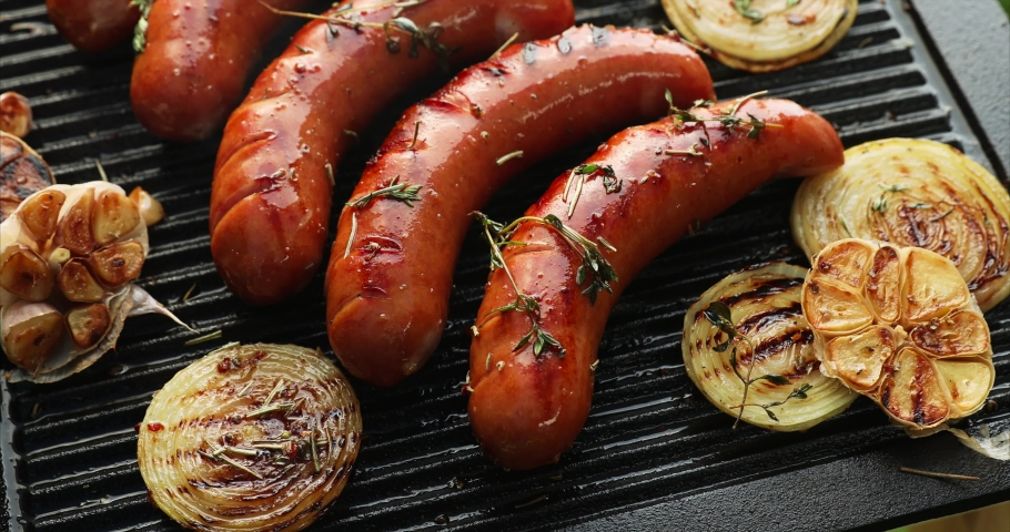 Grilling sausage with the addition of herbs and vegetables on the grill plate, outdoors. Grilling food, bbq, barbecue, 4k