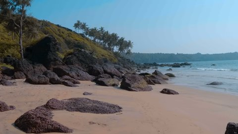 Amazing place, turquoise ocean waves, wild deserted beach, on which volcanic black stones, the dream of any tourist, Goa, India