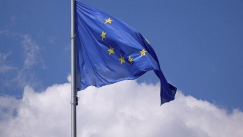 European Union EU Flag Fluttering Against A Blue Cloudy Sky