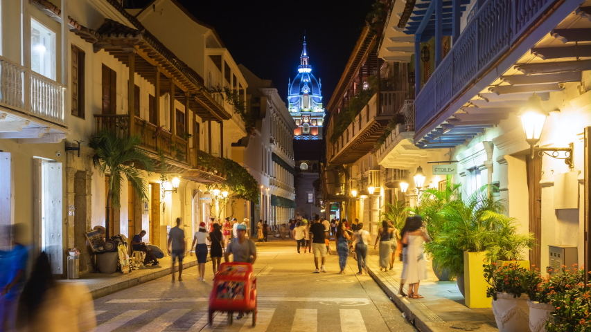 Cartagena de Indias, Colombia - December 10: Night time lapse view of tourists on the streets of the Walled City showing architectural landmark Cartagena Cathedral in Cartagena, Colombia.