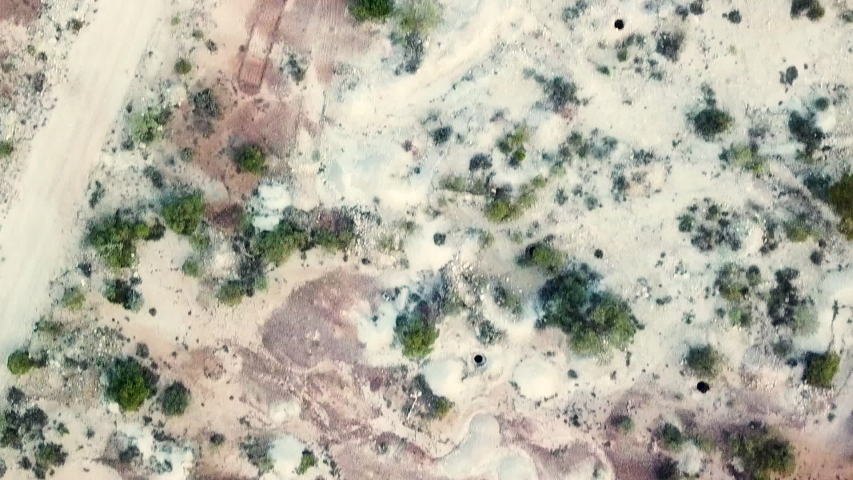 Aerial shot looking straight down showing dispersed opal mining holes in Australian Outback. Location Lightning Ridge, Australia.