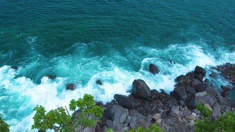 Sea waves crushing to rocky cliff with spray and white foam. Ocean waves splashing to rocky island top view. Turquoise sea surf on stony beach background