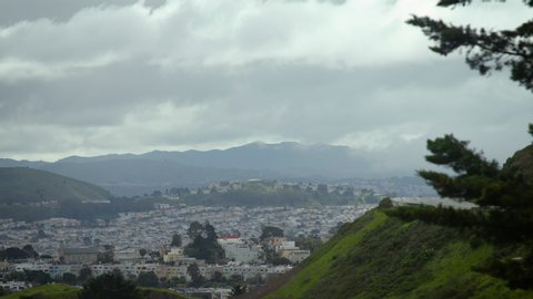 View of houses and buildings on a hill with fog in the distance on a grey cloudy day. Shot on a Canon C200 in 4K in San Francisco in 2019.