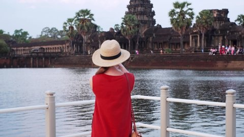 Back of woman taking photo of Angkor Wat temple from bridge. The temple was built in 12th century by khmer civilization and dedicated to Vishnu. Cambodia