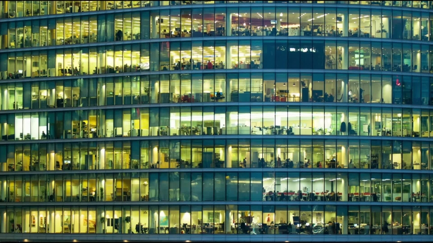 LONDON / UNITED KINGDOM  -  2014 : The exterior of an office block at night revealing the daily activity of office workers night themes of routines working late  #1030714100