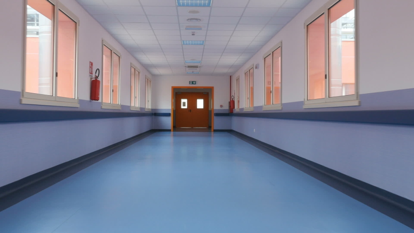 Passage through a long empty corridor. Long empty corridor of a large building. First Person View | Shutterstock HD Video #1030727600