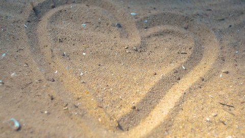 Woman playing with the sand on the beach. Woman. Arm. Beach. Ocean. Sea. Love. Heart. Man