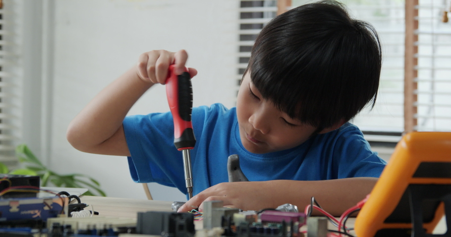 Boy try to fixing computer board in school science club. Project for engineering club in school. People with technology concept. | Shutterstock HD Video #1030817210