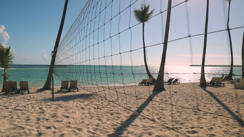 Volleyball net on tropical beach, sunrise and caribbean sea. Punta Cana, Dominican Republic | Shutterstock HD Video #1030857410