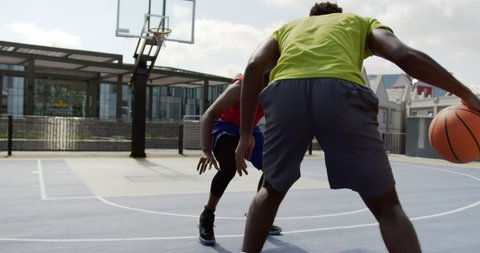 Front view of African american basketball players playing basketball in basketball court. They are dodging basketball