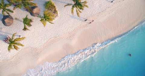 Aerial view of sea waves, umbrellas, palm trees and walking people on sandy beach at sunset. Summer in Zanzibar, Africa. Tropical landscape with parasols, sand, blue water. Top view from air. Travel