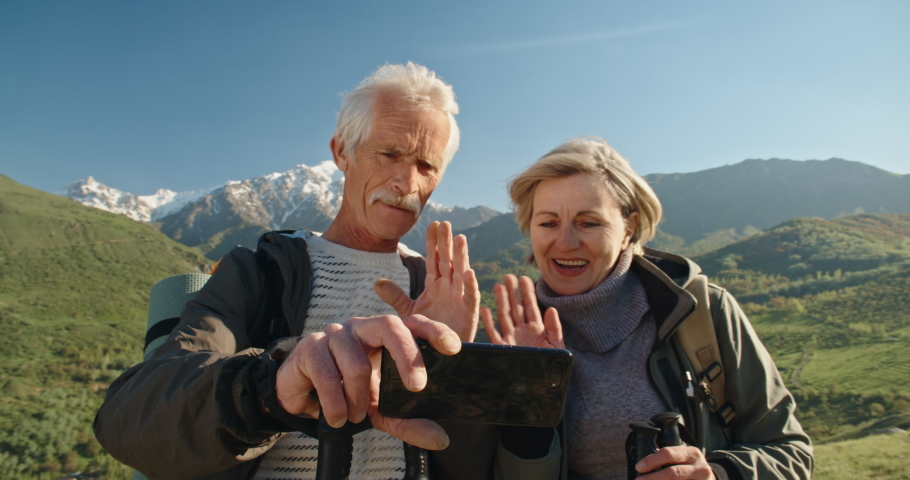Mature caucasian couple travelling together, having a nordic walking hike in spring mountains, then stopping to take a picture on smartphone, spending time after retirement - recreational pursuit #1030971920