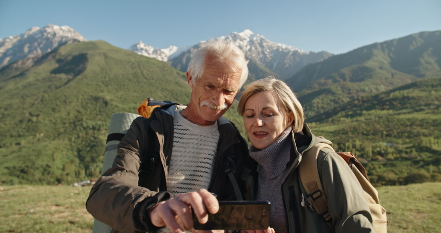 Old couple having a hike in spring mountains, then stopping to take a picture on a smartphone. Senior caucasian family spending time together travelling after retirement - tourism concept 4k #1030971950