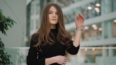 Attractive young woman with brown eyes, long hair, with nails French manicure, with watches in black turtleneck looks to camera, straightens her hair, gives a lovely playful smile. Slow motion