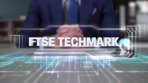 Businessman Writing on Hologram Desk Tech Word- FTSE TECHMARK