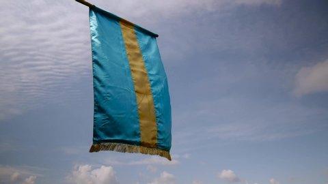 Hungarian  Transylvanian Szekler flag waving in the wind against blue sky.