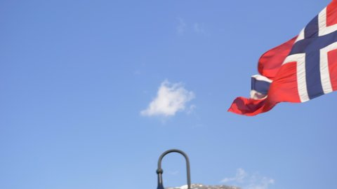 Slow Motion Pan of a Norwegian Flag Blowing in the Wind with a Vibrant Blue Sky in the Background