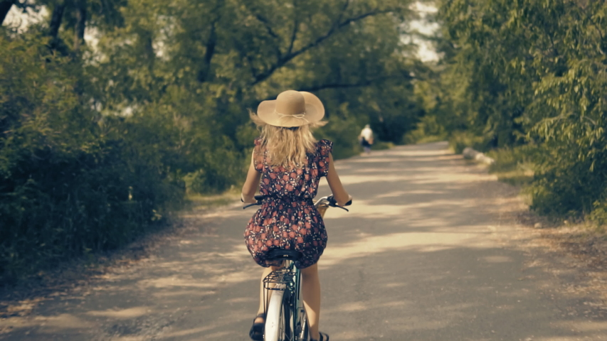 Cyclist Woman On Bicycle.Hair Blowing When Cycling Girl Riding On Bicycle.Bicyclist Woman On Retro Bike.Beautiful Woman Hair Fluttering.Beautiful Cyclist Girl Wearing Dress Rides On City Park . | Shutterstock HD Video #1031089130