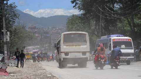 KATHMANDU, NEPAL - CIRCA JUNE 2019: Static shot of Kathmandu ring road at Chabahil, the Himalayas are visible in the background. Pedestrians walking past on the left side.