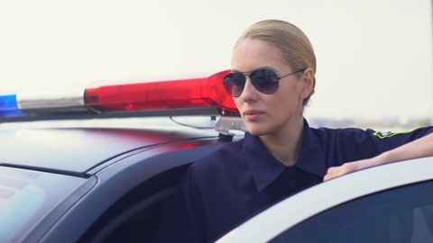 Policewoman in sunglasses smiling, looking into camera, standing near patrol car
