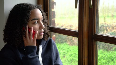 Sad depressed unhappy biracial mixed race African American girl teenager young woman wearing a blue hoodie, sitting by a window phone call talking on her mobile cell phone