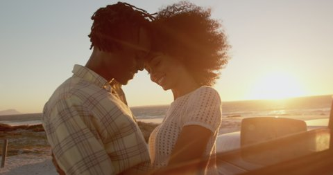 Side view close up of African american couple embracing each other near pickup truck at beach. They are smiling