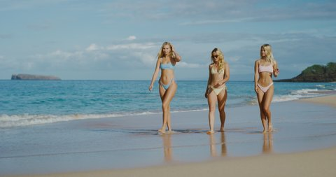 Three beautiful blonde girls walking on the beach in slow motion, baywatch summer theme
