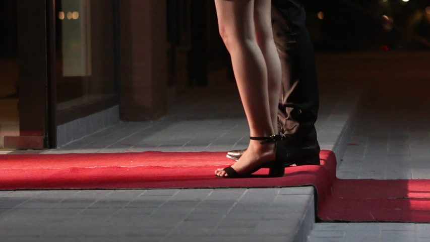 Low angle view of people arriving at a formal event and walking a red carpet as they enter. Women in heels and dresses. Celebrities walk the red carpet. Movie stars arrive for a premier. | Shutterstock HD Video #1031305400