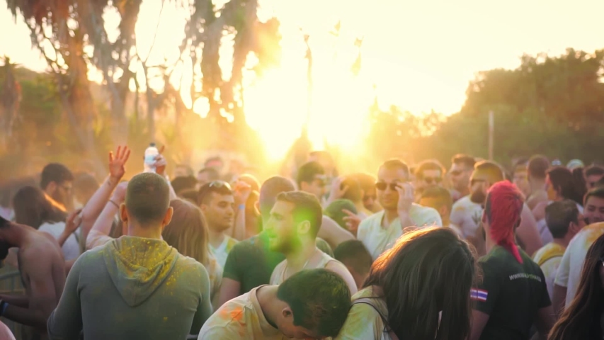 Pembroke, Malta - May 1st 2019:Holi Festival and a group of youthful and happy people dancing covered in different color powders.  #1031305640